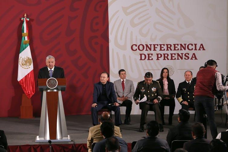 Le président mexicain s'exprime sur une scène avec une petite foule de représentants du gouvernement assis à proximité